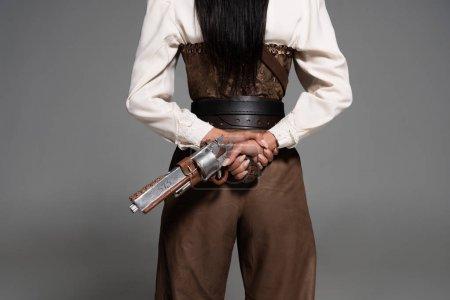 Photo pour Vue recadrée de femme steampunk retenant le pistolet de cru sur le gris - image libre de droit