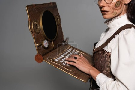 Photo pour Cropped view of steampunk woman using vintage laptop isolated on grey - image libre de droit