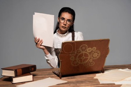 steampunk femme en lunettes avec documents et ordinateur portable vintage sur le lieu de travail isolé sur gris