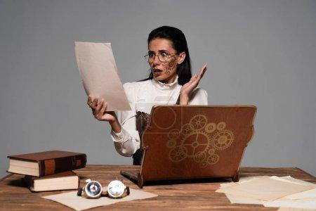 Photo pour Femme steampunk inquiet s'asseyant à la table avec l'ordinateur portatif et les livres d'époque et regardant des documents isolés sur le gris - image libre de droit