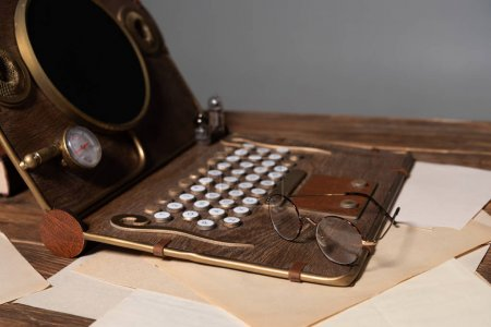 steampunk laptop, glasses and documents on wooden table isolated on grey