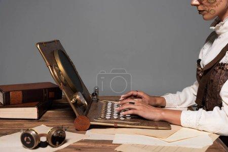 Photo pour Vue recadrée de femme tapant sur l'ordinateur portatif de steampunk à la table d'isolement sur le gris - image libre de droit
