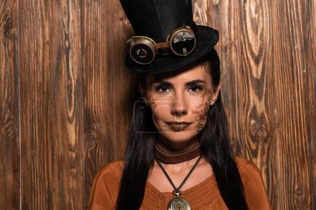 Photo pour Vue avant de la femme de steampunk dans le chapeau supérieur avec des lunettes regardant l'appareil-photo sur le bois - image libre de droit