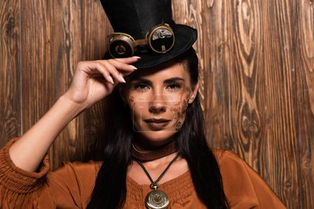 Photo for Front view of steampunk woman touching top hat with goggles looking at camera on wooden - Royalty Free Image