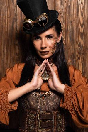 Photo pour Femme attirante avec le médaillon touchant de contact de maquillage de steampunk sur le bois - image libre de droit
