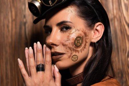 Photo pour Femme pensive de steampunk affichant le geste s'il plaît sur le bois - image libre de droit