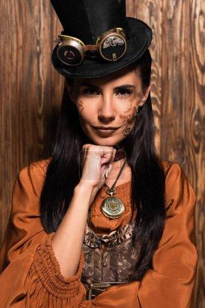 Photo pour Vue avant du menton attirant de femme avec le poing et regardant l'appareil-photo sur le bois - image libre de droit