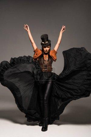 Photo pour Vue pleine longueur de la femme steampunk attrayante dans le chapeau supérieur avec des lunettes restant avec des mains vers le haut sur le gris - image libre de droit