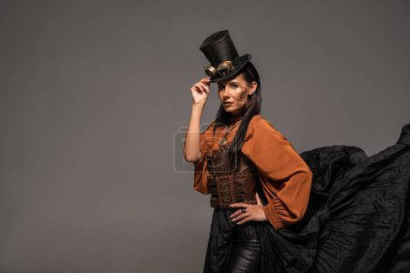 Photo for Steampunk woman in top hat with goggles standing with hand on hip isolated on grey - Royalty Free Image