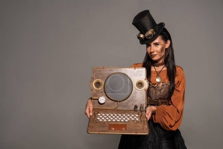 Photo pour Smiling woman in top hat with goggles showing steampunk laptop isolated on grey - image libre de droit