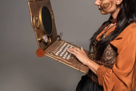 cropped view of woman using steampunk laptop isolated on grey