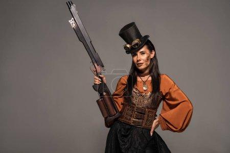 Foto de Atractiva mujer steampunk en el sombrero de copa sosteniendo pistola y de pie con la mano en la cadera aislada en gris - Imagen libre de derechos