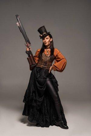 Foto de Vista de longitud completa de la mujer steampunk atractivo en el sombrero de copa sosteniendo pistola y de pie con la mano en la cadera en gris - Imagen libre de derechos
