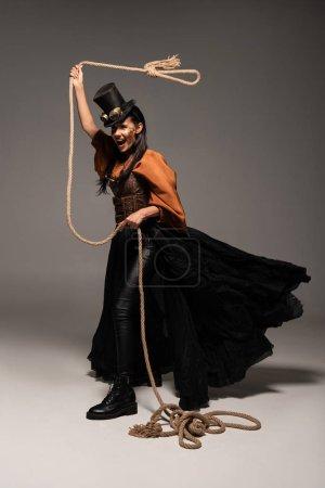 volle Länge Ansicht der schönen schreienden Steampunk-Frau mit Lasso auf grau