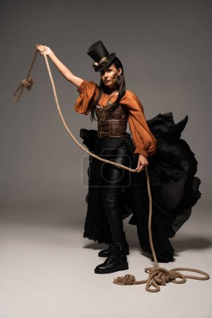 full length view of beautiful steampunk woman holding lasso on grey