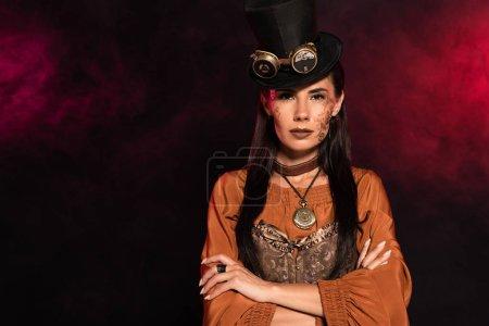 Foto de Vista frontal de la mujer steampunk serio en sombrero superior de pie con los brazos cruzados en negro en humo rosa - Imagen libre de derechos
