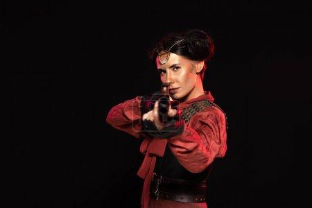 Selektiver Fokus der Steampunk-Frau, die mit Pistole auf Kamera zielt, isoliert auf schwarz