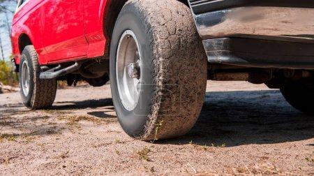 Photo pour Vue recadrée de voiture rouge sur le sol dans la journée ensoleillée - image libre de droit