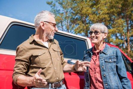 Photo pour Couples aînés dans des lunettes de soleil restant près de la voiture rouge et regardant l'un l'autre dans la journée ensoleillée - image libre de droit