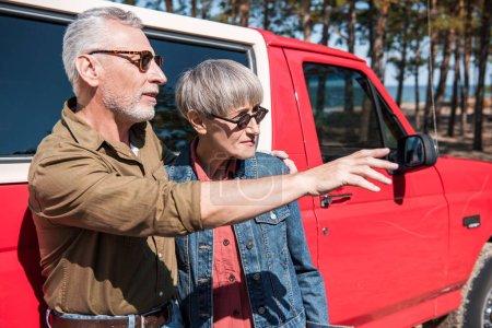 Photo pour Couples aînés dans des lunettes de soleil restant près de la voiture rouge dans le jour ensoleillé - image libre de droit