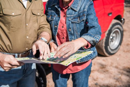 Photo pour Vue partielle de couples de touristes aînés retenant la carte près de la voiture dans la journée ensoleillée - image libre de droit