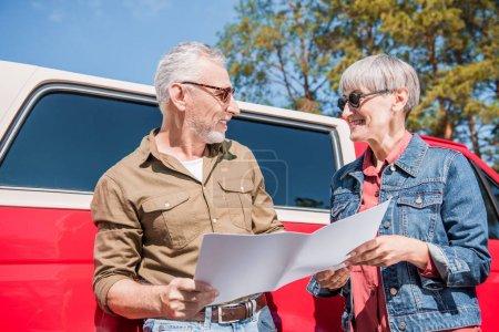 Photo pour Couple de voyageurs aînés dans des lunettes de soleil restant près de la voiture rouge, retenant la carte et regardant l'un l'autre avec le sourire dans la journée ensoleillée - image libre de droit
