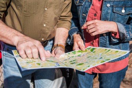Photo pour Vue partielle de couples de touristes aînés retenant la carte dans la journée ensoleillée - image libre de droit