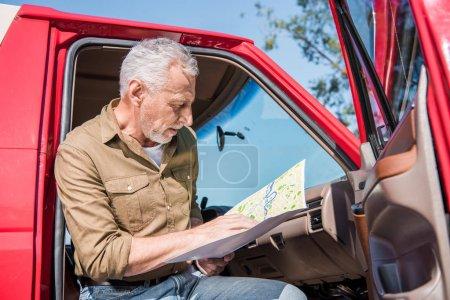Photo pour Voyageur aîné s'asseyant dans la voiture et retenant la carte dans le jour ensoleillé - image libre de droit