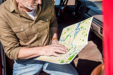 Photo pour Vue recadrée du voyageur aîné s'asseyant dans la voiture et retenant la carte dans la journée ensoleillée - image libre de droit