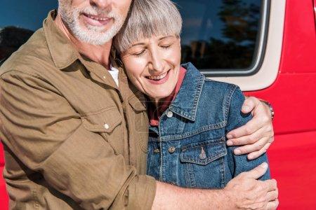 Photo pour Vue recadrée de couple aîné de sourire de touristes restant près de la voiture rouge et embrassant dans la journée ensoleillée - image libre de droit
