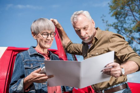 Photo pour Couples aînés de voyageurs restant près de la voiture et regardant la carte dans la journée ensoleillée - image libre de droit