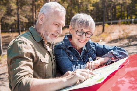 Photo pour Couples aînés de sourire des voyageurs restant près de la voiture et regardant la carte dans la journée ensoleillée - image libre de droit