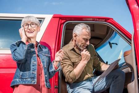 Photo for Senior woman in glasses talking on smartphone while husband sitting in car and looking at map - Royalty Free Image