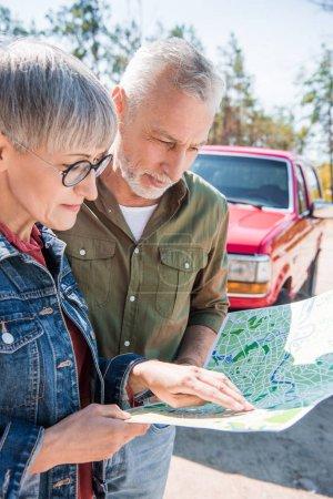 Photo pour Couples aînés de touristes restant près de la voiture et regardant la carte dans la journée ensoleillée - image libre de droit