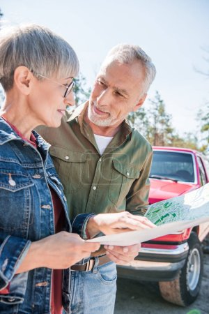 Photo for Senior couple of tourists holding map and looking at each other in sunny day - Royalty Free Image