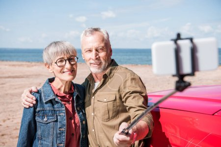 Photo for Smiling senior couple embracing and taking selfie in sunny day - Royalty Free Image