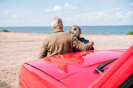 Foto de Vista trasera de la pareja de la tercera edad de pie cerca de coche rojo en la playa y abrazando en el día soleado - Imagen libre de derechos