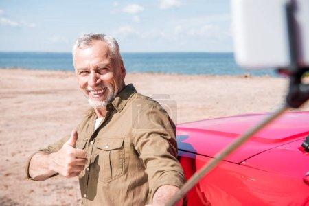 Photo pour Homme aîné de sourire restant près de la voiture rouge et prenant le selfie tout en affichant le pouce vers le haut dans le jour ensoleillé - image libre de droit
