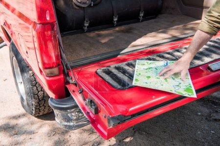 Photo pour Vue recadrée de l'homme avec la carte près de la voiture rouge dans le jour ensoleillé - image libre de droit
