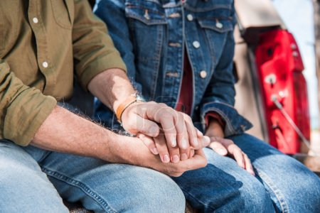 Foto de Vista recortada de la pareja de la tercera edad en jeans que se sostienen de la mano - Imagen libre de derechos