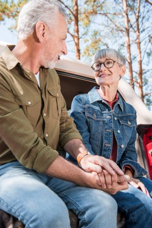 Photo for Senior couple in jeans holding hands and looking at each other with smile - Royalty Free Image