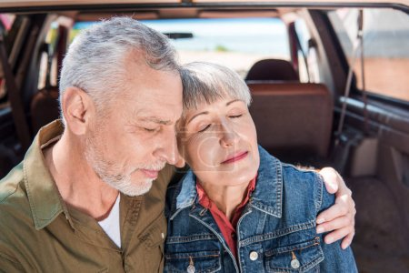 Photo for Senior couple embracing with closed eyes near car - Royalty Free Image