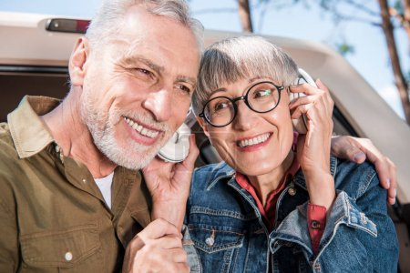 smiling senior couple of tourists listening music in headphones