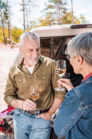Photo pour Couples aînés heureux restant près de la voiture avec des verres de vin et regardant l'un l'autre - image libre de droit