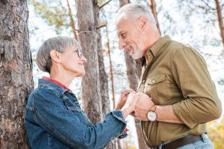 Photo for Happy senior couple holding hands and looking at each other near car in forest - Royalty Free Image