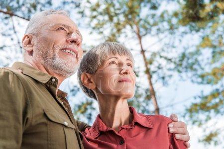 Photo pour Vue inférieure du couple aîné heureux embrassant et souriant dans la forêt - image libre de droit