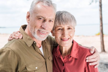 Photo for Happy senior couple embracing and smiling at beach - Royalty Free Image