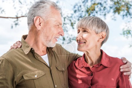 Photo for Happy senior couple embracing and looking at each other with smile in forest - Royalty Free Image