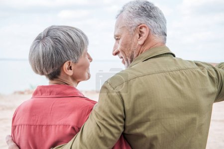 Photo for Back view of senior couple embracing and looking at each other at beach - Royalty Free Image