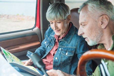 Photo pour Focus sélectif de couples aînés regardant la carte dans la voiture - image libre de droit